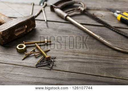 cross head bolt screws thread with nails hammer and a handsaw on a wooden table in the workshop closeup with copy space