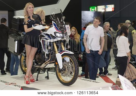 BRNO, CZECH REPUBLIC-MARCH 4,2016: Beautiful hostesses present motorcycle Honda CRF1000L Africa Twins DCT on International Fair for Motorcycles on March 4,2016 in Brno in Czech Republic