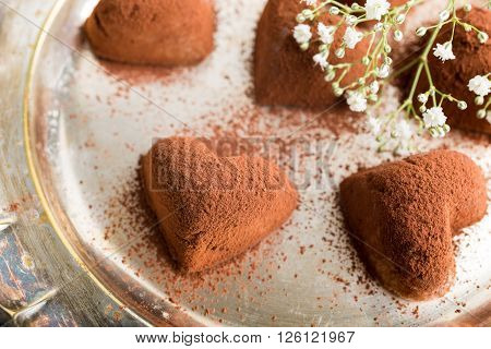 Handmade candies Tiramisu in eart shape on metal plate. Valentine's Day and Mother's Day concept. Top view.