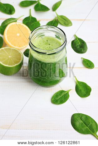 Glass jar of fresh summery drink green smoothie, spinach leaves, lime fruit. Vertical.