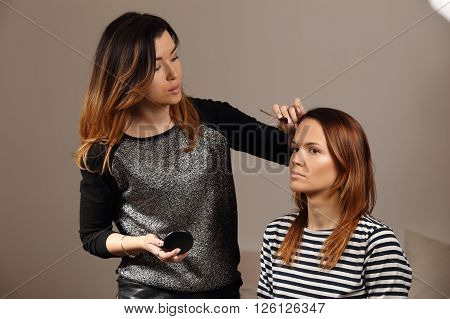 Close-up of the work of professional make-up artist. Girl doing make-up to the client, and apply on face bronzer.