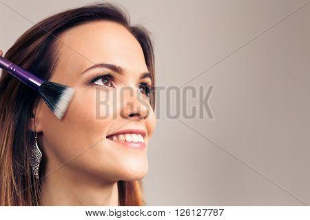 Makeup artist applies skintone on client face. Beautiful woman smiling face. Perfect makeup. Skincare foundation. The process of working professional makeup.