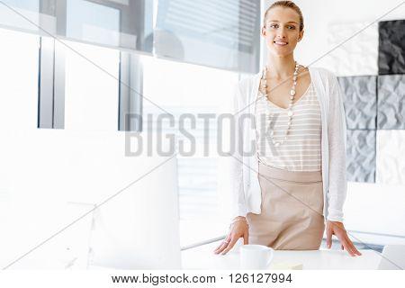 Attractive office worker standing next to window