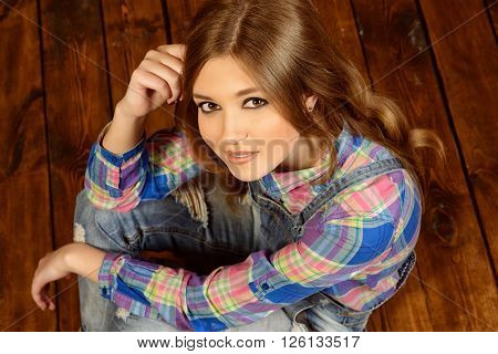 Pretty teen girl in casual jeans clothes sitting by a wooden wall. Youth style.