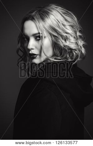 Black-and-white portrait of a blonde young woman with dark dramatic make-up.