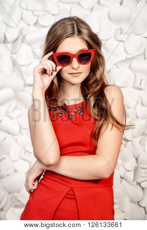 Pretty woman in red dress and sunglasses in pin-up style stands by a background of white paper flowers. Spring and summer concept. Fashion shot.