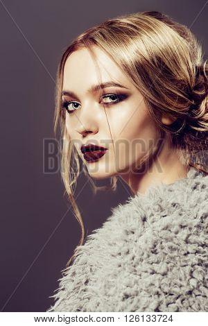 Vogue shot of a beautiful young woman with dark make-up. Cosmetics, maroon lipstick. Studio shot.