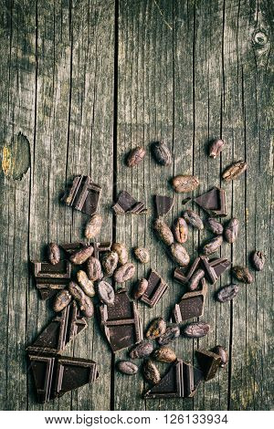 dark chocolate and cocoa beans on old wooden table