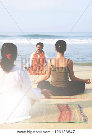 Yoga Instructor And His Students By The Beach Concept