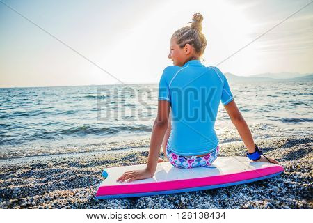 Happy Surfing girl on a beach looking on the sea and ready to go into the water. Sunset time.