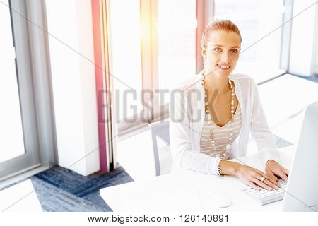 Attractive office worker sitting at desk