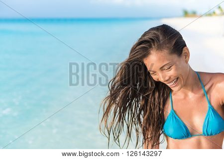 Happy beautiful Asian mixed race ethnic bikini body woman laughing having fun relaxing on tropical summer beach on Caribbean travel holidays. Brunette with healthy hair.