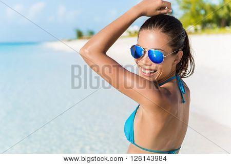 Sexy bikini beach woman having fun dancing in the sun relaxing laughing wearing blue fashion mirror sunglasses. Blissful young girl enjoying summer holiday travel on tropical vacation.