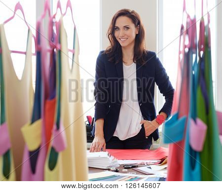 Beautiful young designer in her fashion atelier showroom.