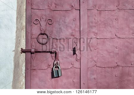 Aged dark pink steel door with rivets and aged metal door handle in the form of stylized lily. Textured grunge background.