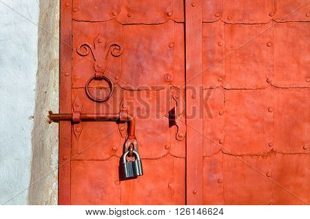 Aged bright orange steel door with rivets and aged metal door handle in the form of stylized lily. Grunge background.