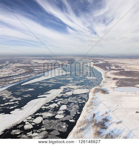 Aerial view of the great river with floating ice floes during the spring days. Drifting of ice. Driving ice floe.