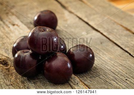 Bunch of round plums set on old wooden surface