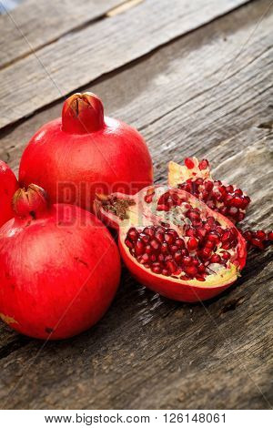 Two fresh red pomegranate fruits, with one peeled piece and seeds, set on old wooden surface