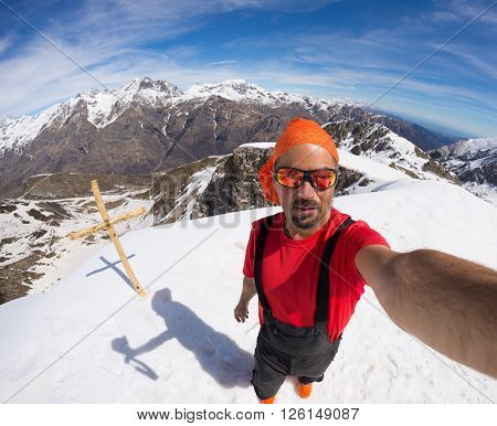 Adult alpin skier with beard sunglasses and hat taking selfie on snowy in the beautiful italian Alps with clear blue sky. Concept of wanderlust and adventures on the mountain. Wide angle fisheye lens.