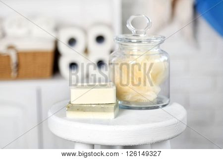 Bathroom set with wisp and soaps on stool in light interior