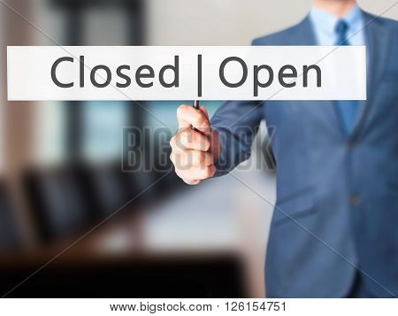 Open Closed - Businessman Hand Holding Sign