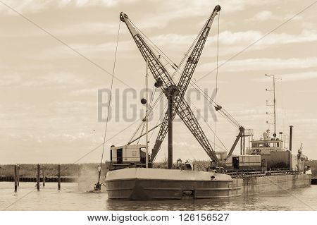Effect vintage. Dredger ship navy working to clean a navigation channel