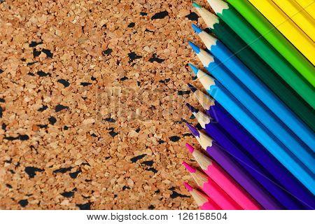 Colour pencils on cork board background.