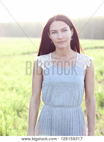 Beautiful girl in a dress in the summer resting enjoying the idea of lifestyle, fashion concept, the nature of woman, portrait of a girl in a summer park
