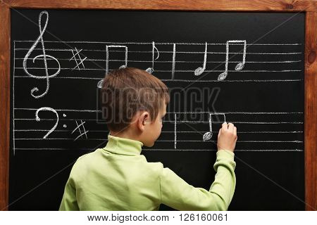Cute boy writing at the blackboard with musical notes, in the classroom