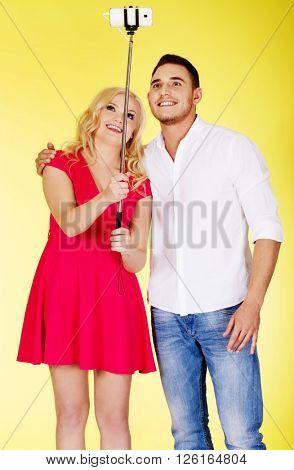 Happy couple taking selfie photo with selfie stick