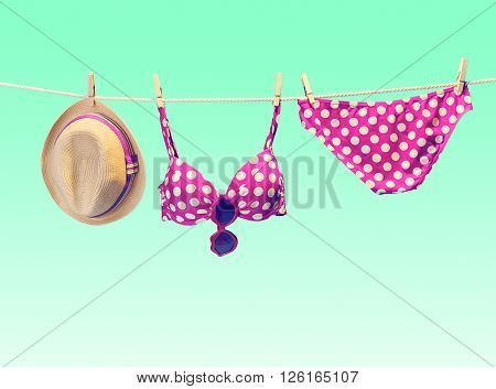 Beach outfit. Summer clothes and accessories stylish set. Fashion swimsuit bikini pink polka dots, sunglasses, hat on rope. Essentials creative tropical look. Ocean sea vacation concept, vintage
