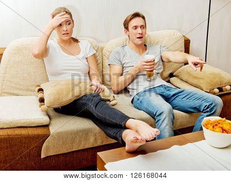 Woman sitting bored while man watching sports