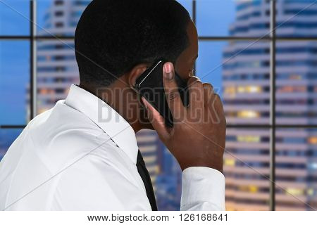 Afro man with mobile phone. Businessman's phonecall on skyscraper background. Evening business negotiations. End of the working day.