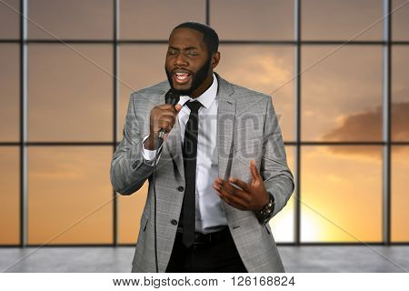 Black singer holding microphone. Singing man on sunset background. Top blues vocalist on stage. Star of local talent show.