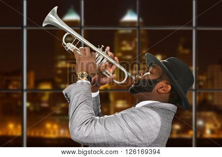 Darkskinned trumpeter in fedora hat. Trumpeter playing in night megalopolis. Music and passion are one. Young talent from capital city.