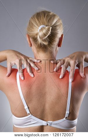 Woman with pain in shoulders. Pain in the human body with red dot on a gray background