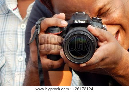 HYDERABAD,INDIA-MARCH 27:Indian young adult man shoot an event with Digital Camera on March 27,2016 in Hyderabad,India
