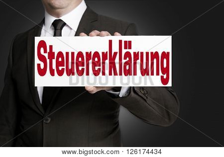 steuererklärung (in german tax return) sign is held by businessman.