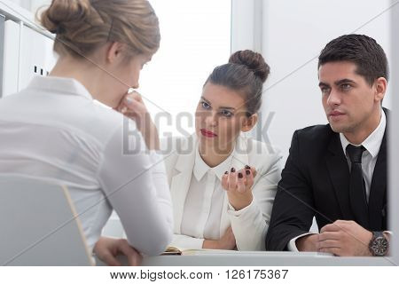 Pretty professional boss asking a question to an intern