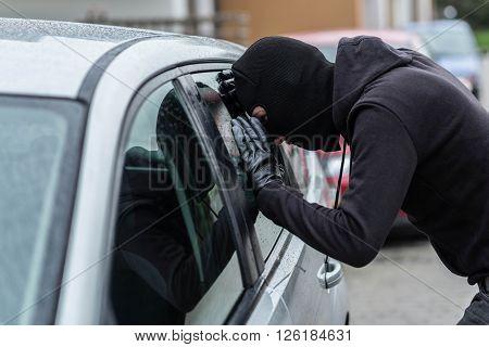 Car Thief Looking Through Car Window