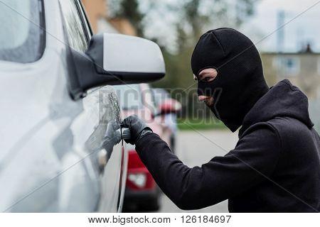 Car Thief Pulls The Handle Of A Car.