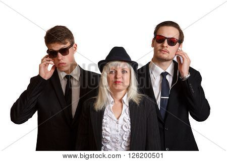 A well dressed woman with two young bodyguards in suits