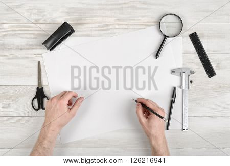 Closeup hands of man holding pencil and draw on white paper in top view. Workplace of draftsman equipped with pencil, ruler, pen, stapler, scissors and magnifying glass. Working process.