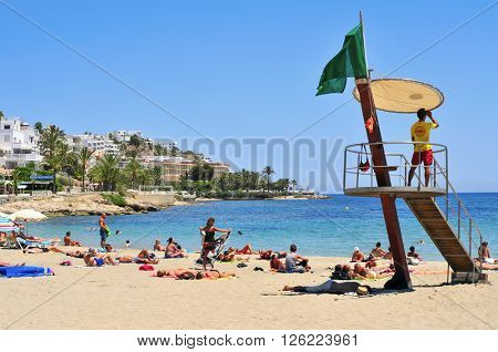 IBIZA, SPAIN - JUNE 19, 2015: Lifeguard tower and sunbathers in the popular Ses Figueretes Beach, in Ibiza Town, Spain. Ibiza is a well-known summer tourist destination in Europe