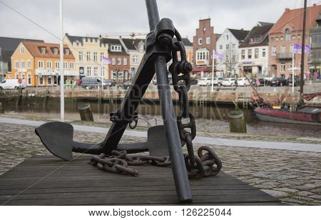 Anchor at Husum harbor with the harbor's houses in backgound