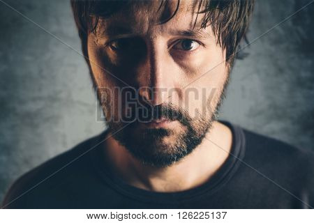 Dramatic low key portrait of adult male headshot of sad lonely unshaven person selective focus