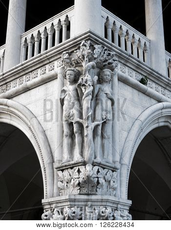 Adam and Eve expelling them from Paradise. The sculpture on the church of St. Mark. Italy. Venice.
