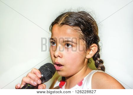 Nine year old girl singing with microphone