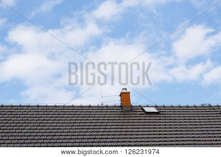 brown roof with chimney and Lightning conductor - blue sky